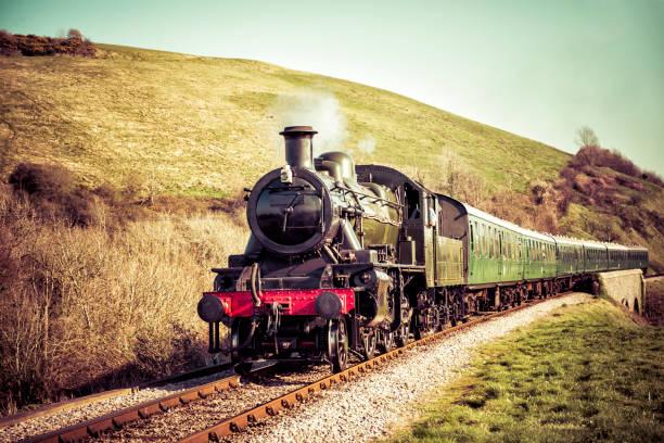 dampfzug bewegt sich sanft durch die englische landschaft - lokomotive stock-fotos und bilder