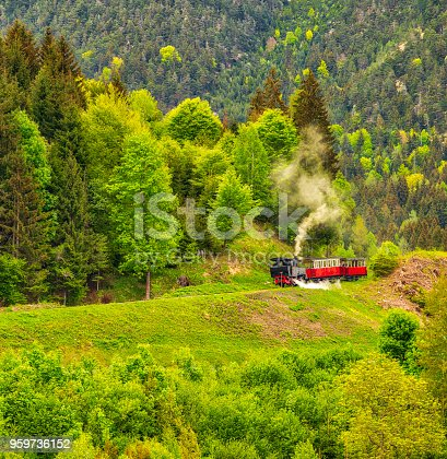 an old steam train is crossing the green hill in the Alp mountains