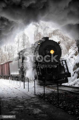 Steam train entering railroad tunnel with black locomotive smoke boiling against ceiling, yellow headlight shining yellow in the darkness.