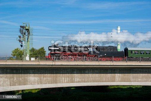 Steam train on a bridge. Sunny summer day.