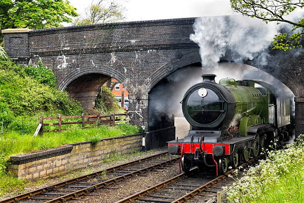 Steam train passing under a bridge stock photo