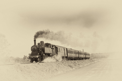 Ancient steam train running on tracks in the countryside. Old photo filter applied.