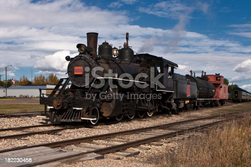 A vintage steam locomotive pulling a short train.
