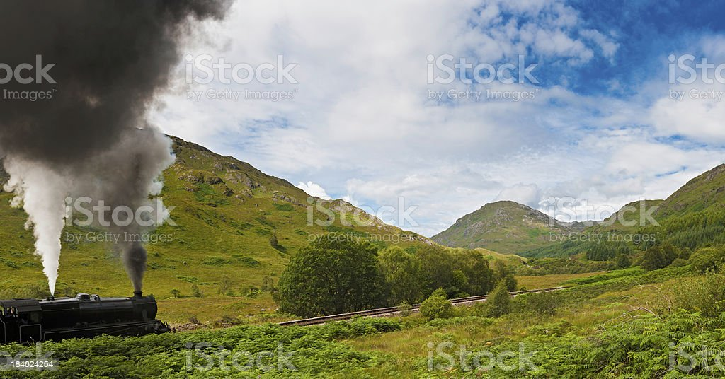 Steam train rushing through Highland mountain glen Scotland stock photo