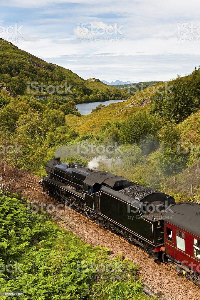 Steam train rushing through idyllic Highland mountain glen stock photo