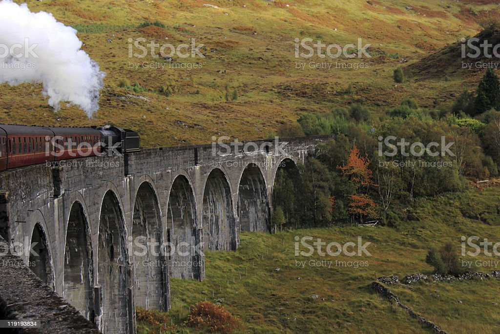 Steam train travelling across the Glenfinnan Viaduct stock photo