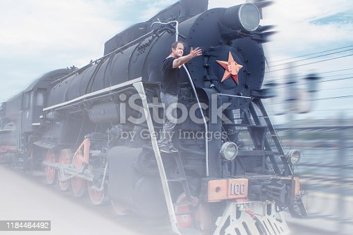 Steam train with a man on the footboard. Man indicates the direction of the steam locomotive. Platform in the smoke from the arriving train. Retro style, old train times of the 19th - 20th century.