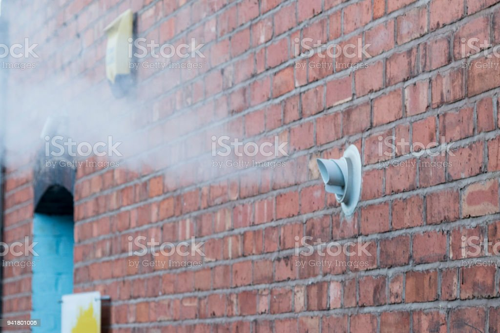 Steam vent from a gas boiler on a brick wall stock photo
