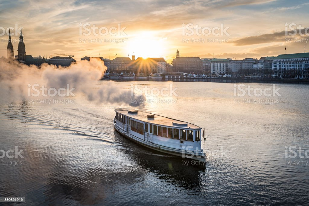 steamboat on Alster Lake in Hamburg, Germany with cityscape in background during sunset stock photo