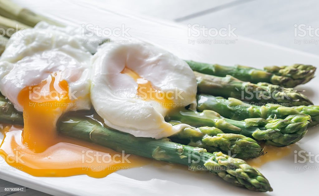 Steamed asparagus with poached eggs stock photo