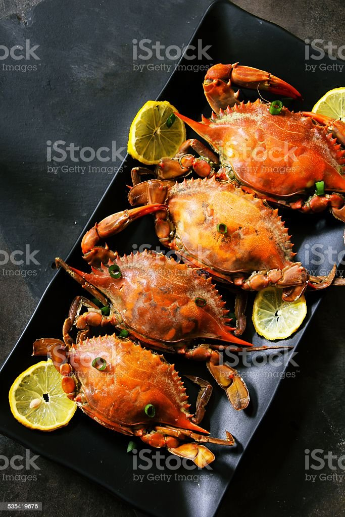 Steamed Blue crabs with lemon garnish stock photo