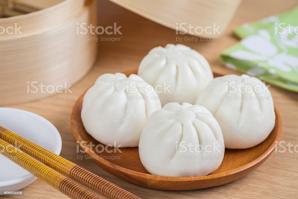 Steamed buns on wooden plate and bamboo steamer basket stock photo