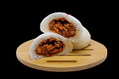 Steamed buns with red pork filling on a wooden tray and a black background