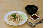 Steamed chicken with rice in white plate on the wood table with space for text.