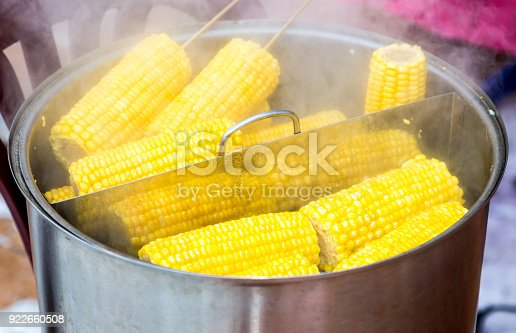 Steamed corn with a wooden plug in a cooking saucepan, street food. Boiled the corns with a bit of sugar or salt to get a delicious taste