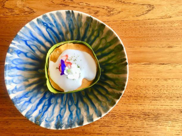 gedünsteten fisch curry kuchen mit kokosmilch und dekoration mit frischen blumen in bananenblatt legen sie indigo design muster gericht holztisch. - marinekuchen stock-fotos und bilder