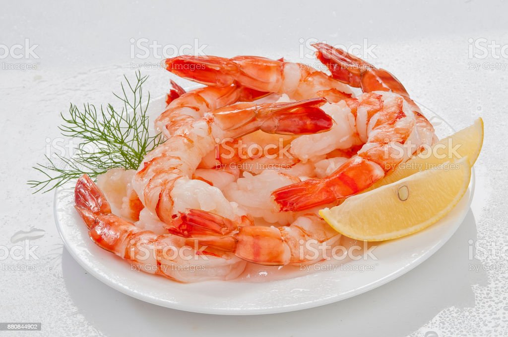 Steamed Jumbo headless shrimps with deli leaves and Lemon on white plate on white background stock photo
