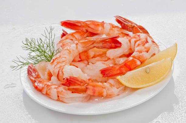 Steamed Jumbo headless shrimps with deli leaves and Lemon on white plate on white background stock photo