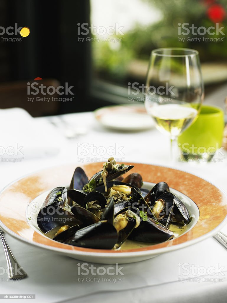 Steamed Mediterranean mussels, glass of wine in background foto stock royalty-free
