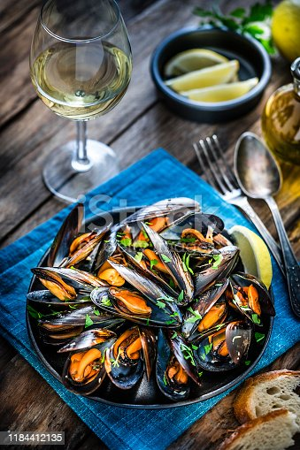 High angle view of steamed mussels in a black plate and white wine glass shot on bluish tint background. Sliced lemon and bread pieces complete the composition. Selective focus on mussels. Predominant colors are black, orange and blue. XXXL 42Mp studio photo taken with Sony A7rii and Sony FE 90mm f2.8 macro G OSS lens