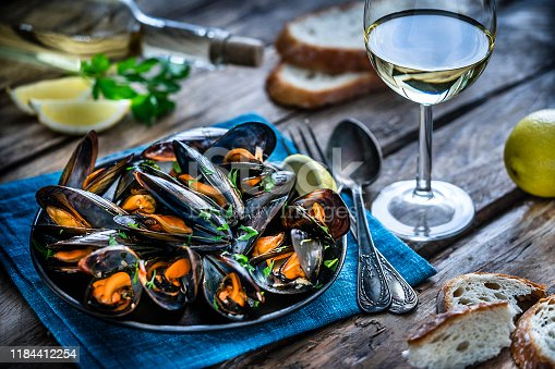 High angle view of steamed mussels in a black plate and white wine glass shot on rustic wooden table. Sliced lemon and bread pieces complete the composition. Selective focus on mussels. Predominant colors are black, orange and blue. XXXL 42Mp studio photo taken with Sony A7rii and Sony FE 90mm f2.8 macro G OSS lens