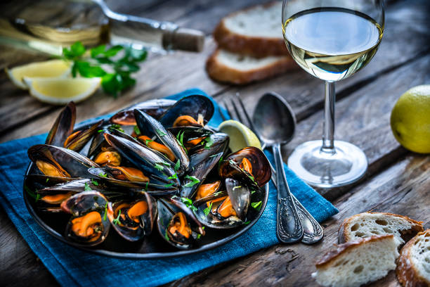 Steamed mussels and white wine on rustic wooden table High angle view of steamed mussels in a black plate and white wine glass shot on rustic wooden table. Sliced lemon and bread pieces complete the composition. Selective focus on mussels. Predominant colors are black, orange and blue. XXXL 42Mp studio photo taken with Sony A7rii and Sony FE 90mm f2.8 macro G OSS lens mussel stock pictures, royalty-free photos & images