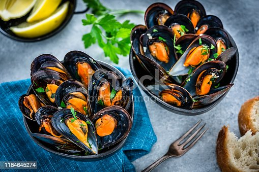 High angle view of steamed mussels in two black bowls shot on bluish tint background. Sliced lemon, parsley twig and bread pieces complete the composition. Selective focus on mussels. Predominant colors are black, orange and blue. XXXL 42Mp studio photo taken with Sony A7rii and Sony FE 90mm f2.8 macro G OSS lens