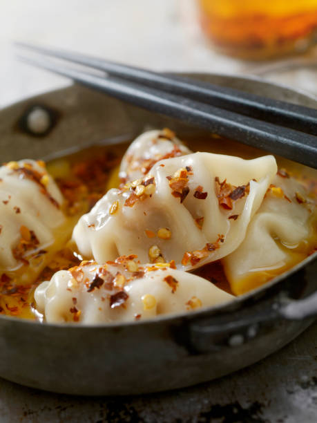 steamed pork dumplings in chili oil - dumplings stock photos and pictures