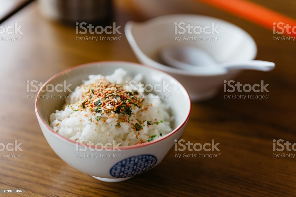 Steamed rice with Japanese seasoning rice flake in white bowl at the restaurant in Hokkaido, Japan. stock photo