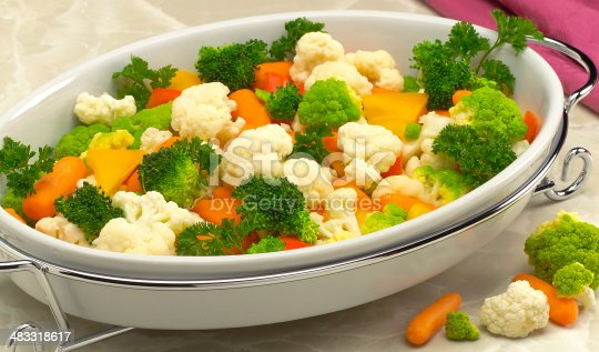 Broccoli, cauliflower, carrots, parsley and orange peppers in formal serving dish