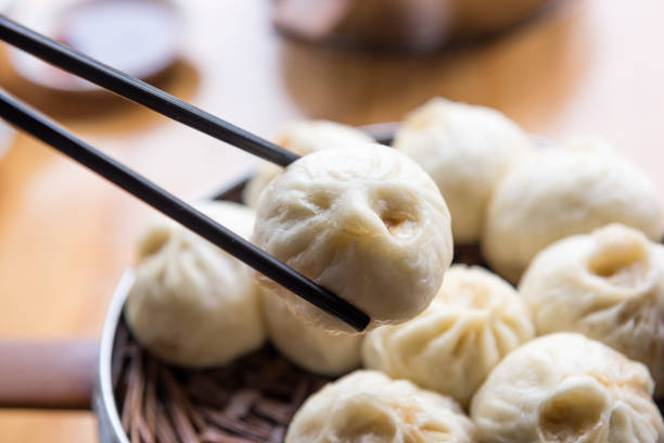 steamed xiaolongbao with chopsticks - dumplings stock photos and pictures