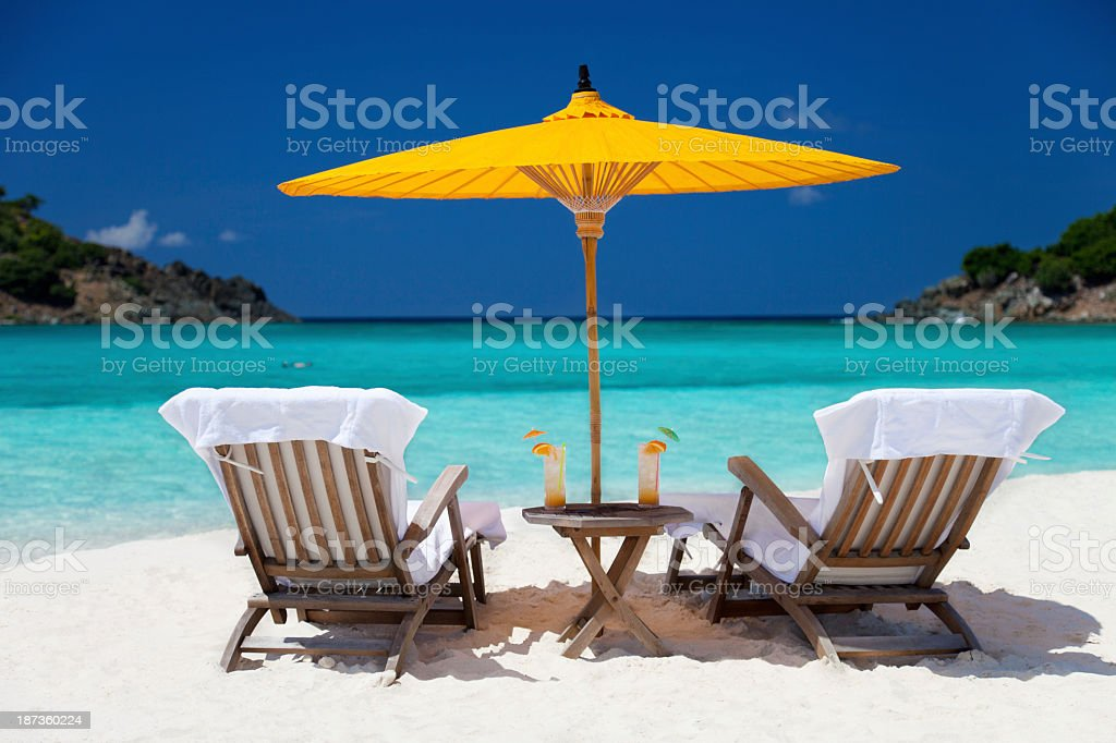 steamers under umbrella at a tropical beach in the Caribbean royalty-free stock photo