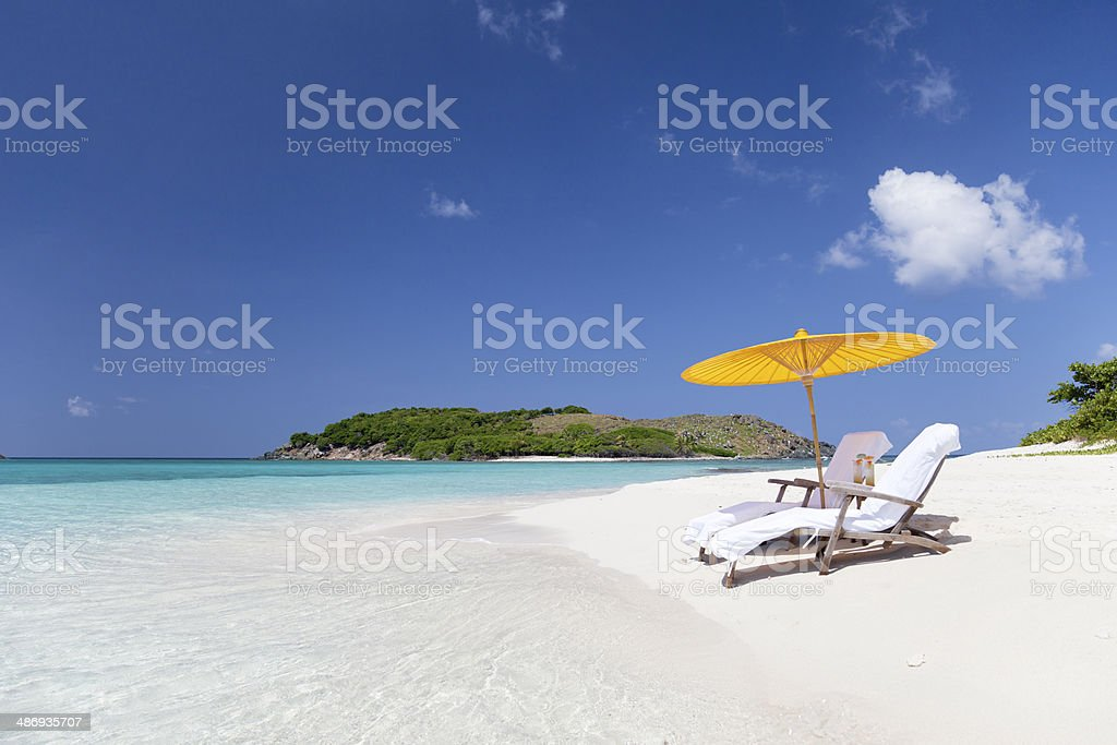 steamers under umbrella at a tropical beach in the Caribbean stock photo