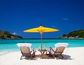 teak steamers under yellow Chineese umbrella at a tropical beach in the Caribbean