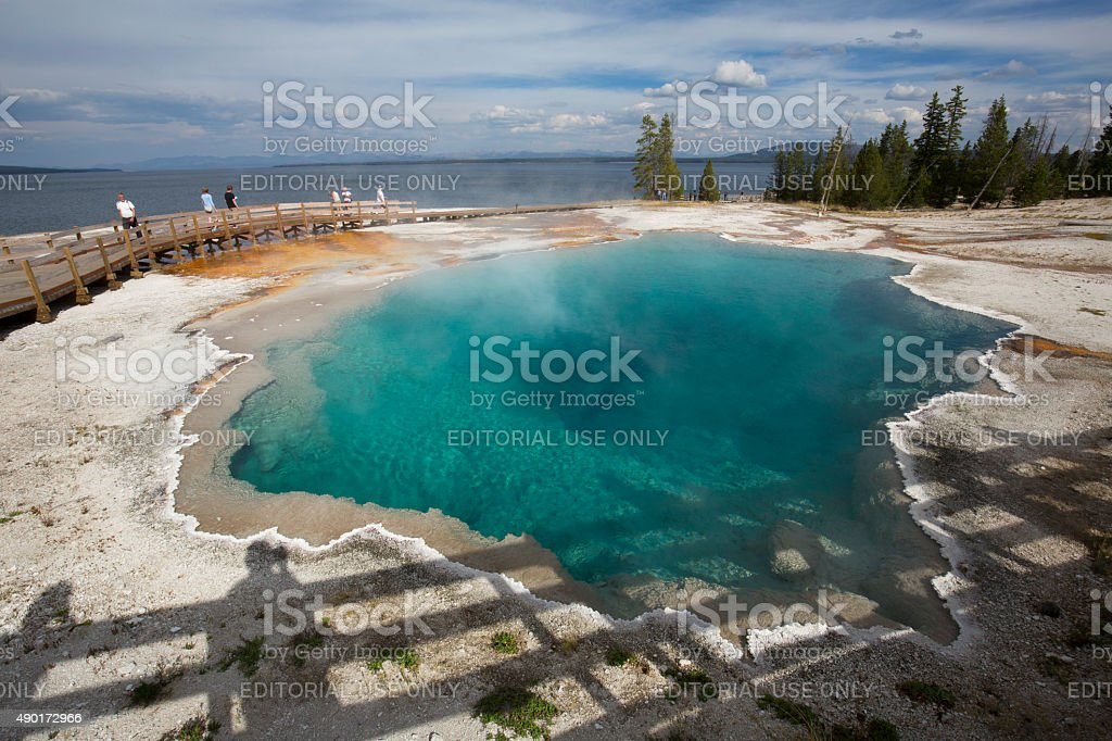 Steaming aqua hot spring, with people on boardwalk, Yellowstone. stock photo