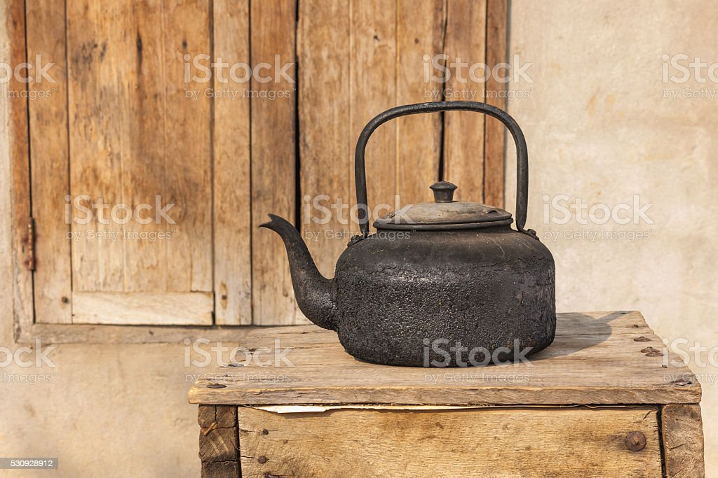 Steaming black tea kettle Thai style in countryside on wooden stock photo