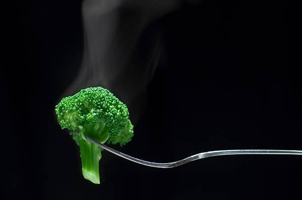 steaming broccoli on a fork - gestoomd stockfoto's en -beelden