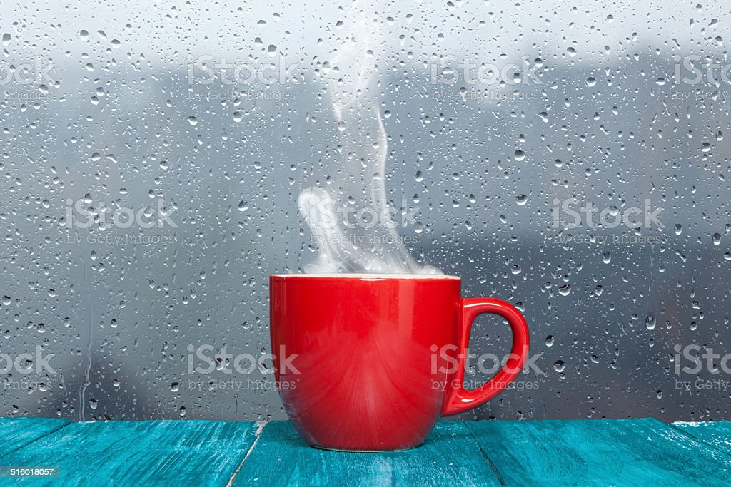 Steaming coffee cup on a rainy day window background stock photo