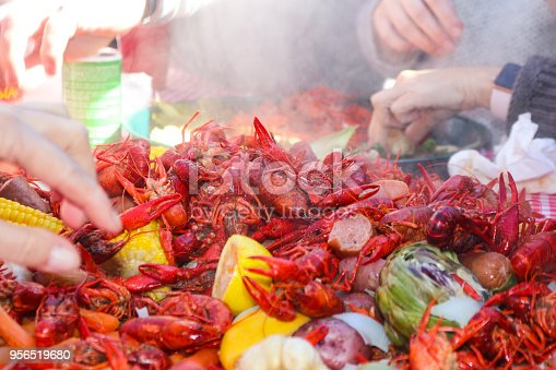 Steaming crayfish and lemons and sausages and artichokes and other vegestables piled on table with multiple hands reaching in to retreive food - selective focus