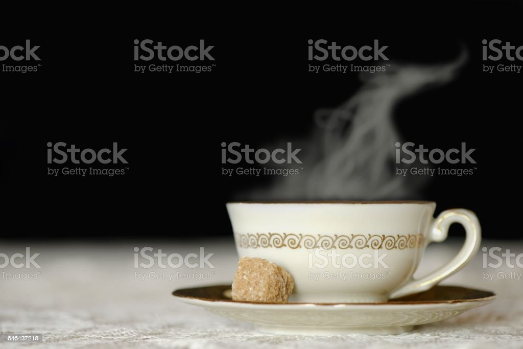Steaming cup of hot tea on a vintage embroidery, isolated on black