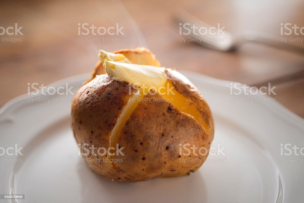 Steaming hot Baked Potato with melting butter. stock photo