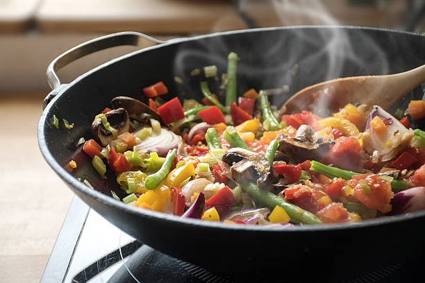 steaming mixed vegetables in the wok, asian style cooking - roeren stockfoto's en -beelden