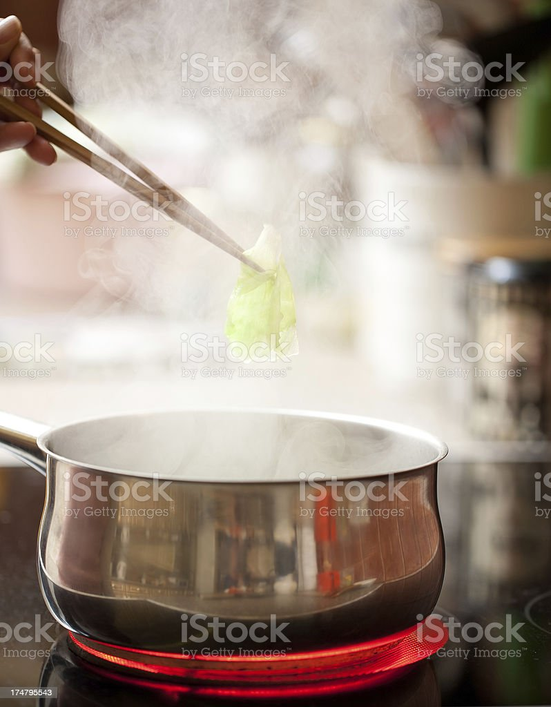 Steaming pan on ceramic hob with chopsticks royalty-free stock photo