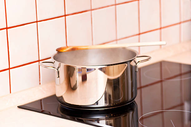 Steaming pot on a ceramic hob stock photo