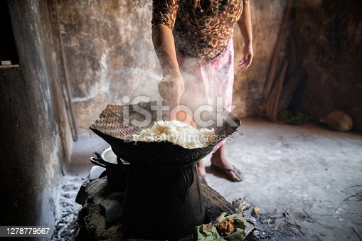 A shot of an unrecognisable Balinese woman standing in in a very basic hut. She is wearing traditional clothing and is steaming rice over an open fire.
