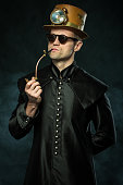 istock Steampunk man in a hat smoking a pipe 1019380214