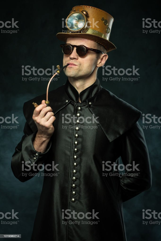 Steampunk man in a hat smoking a pipe stock photo