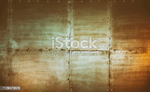Metallic block tile wall with rivets. Industrial abstract background.