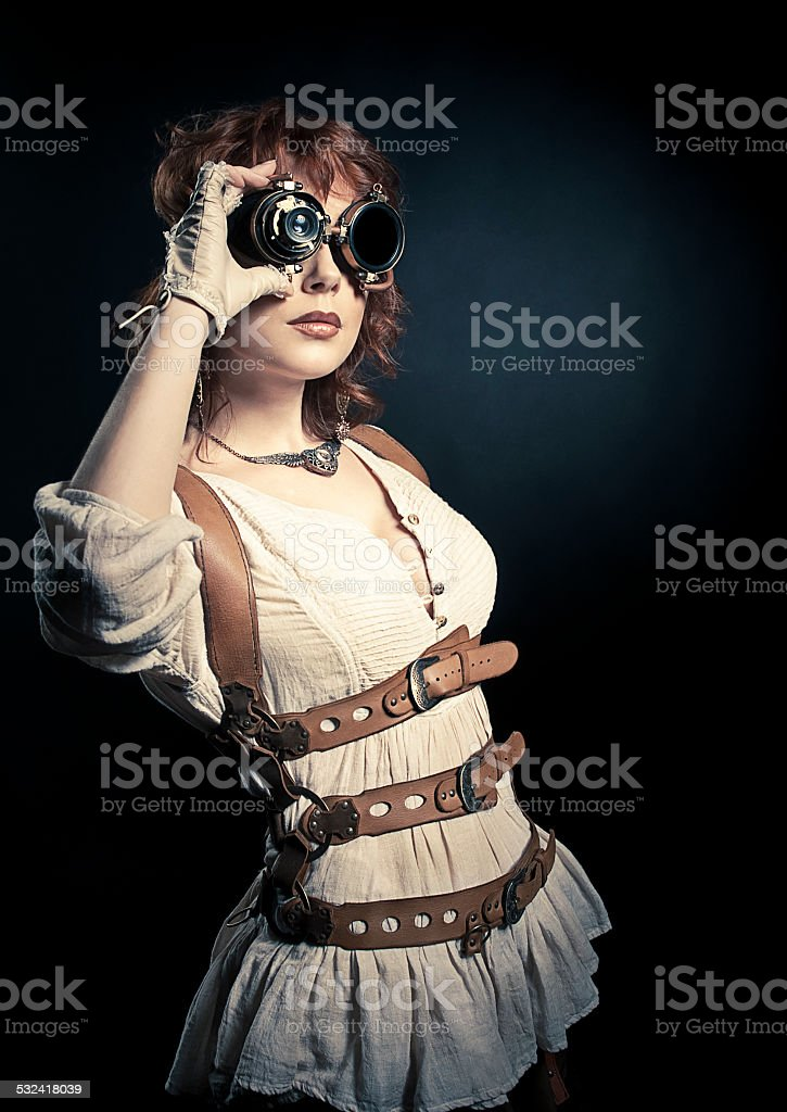 Steampunk woman looking over her goggles stock photo