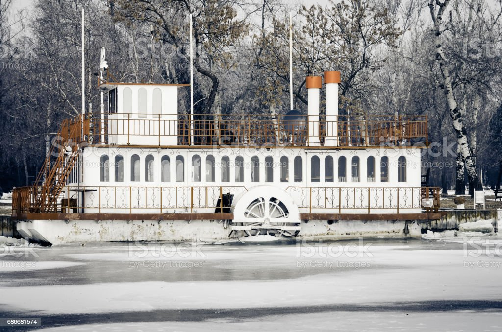 Steamship. Abandoned old rusty steamship stuck in ice of frozen river. stock photo